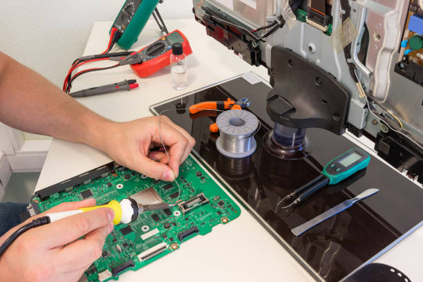 TV repair in the service center, engineer soldering electronic components